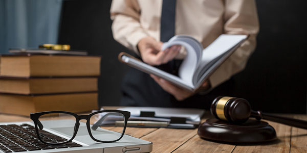 A person reading a book, gavel, glassess on a laptop and 3 books